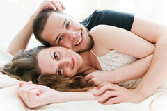 Lovely couple hugging on their bed Royalty Free Stock Images