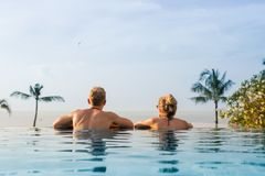 Couple in infinity pool looking at horizon royalty free stock images