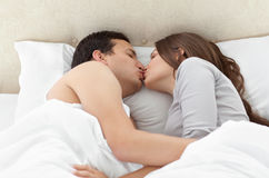 Lovely couple kissing in each other's arms. On the bed at home Royalty Free Stock Photos