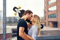 Lovely couple kissing. While standing in a park in the city Royalty Free Stock Photography