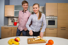 Lovely couple on kitchen. Young women cutting banana with a sly glance in front of her boyfriend cast an intimidated glance stock photos