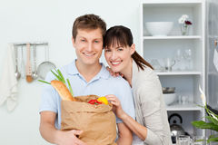 Lovely couple looking at the camera. With their shoping bags at home Stock Images