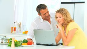 Lovely couple looking at a recipe on internet stock footage