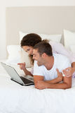 Lovely couple looking at their laptop Stock Photography
