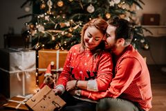 Lovely couple in love opening christmas presents. Together for christmas, holiday joy and happyiness concept royalty free stock photo