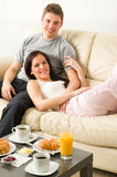 Lovely couple lying on couch in pajamas Stock Photos