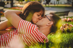 Lovely couple lying on green grass in park, kissing and spending time together.  Royalty Free Stock Photos