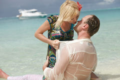 Lovely couple lying on sand and kissing in caribbean island, flo Royalty Free Stock Photography