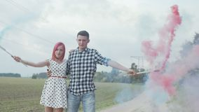 Lovely couple making colored smoke heart outdoors stock footage