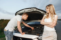 Lovely couple near the car. Car trip. Portrait of a beautiful blond girl with curvy hair standing watching her handsome boyfriend fixing something broken in Royalty Free Stock Photos