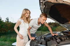 Lovely couple near the car. Car trip. Portrait of a beautiful blond girl with curvy hair standing watching her handsome boyfriend fixing something broken in Stock Photo
