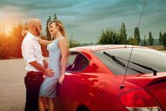 Lovely couple near red sport car. Lovely couple looking at each others and hugging near a red sport car overcast Stock Photography