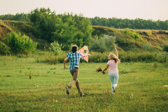 Lovely couple play with air kite at green meadow. At countryside royalty free stock photo