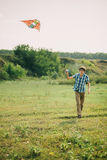 Lovely couple play with air kite at green meadow. Lovely couple play air kite at green picturesque meadow at countryside royalty free stock photo