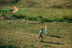 Lovely couple play with air kite at green meadow. Lovely couple play air kite at green picturesque meadow at countryside stock photos