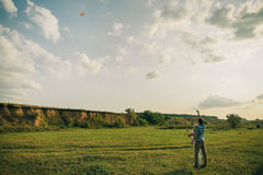 Lovely couple play with air kite at green meadow. Lovely couple play with air kite at green picturesque landscape meadow in countryside stock photography