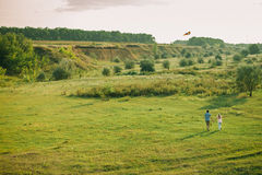 Lovely couple play with sky air kite at green meadow. Lovely couple play with air kite at green picturesque landscape meadow in countryside royalty free stock photography