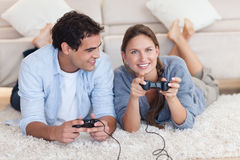 Lovely couple playing video games. While lying on a carpet Stock Photos