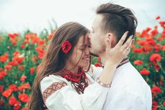 Lovely couple  in the poppy field. Ukrainian traditional clothes Stock Image