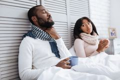 Lovely couple recovering from flu together. Ill couple. Tired nice couple being in bed with cups of tea while recovering from flu together Stock Photo