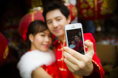 Lovely couple selfie photo by smartphone with red paper chinese. Lantern in Chinese suit Royalty Free Stock Image