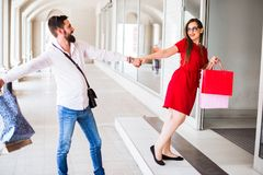 LOVELY COUPLE WITH SHOPPING BAGS ENTERS IN THE STORE royalty free stock photo