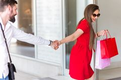 LOVELY COUPLE WITH SHOPPING BAGS ENTERS IN THE STORE stock photo