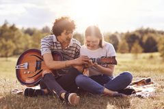 Lovely couple sit cross legs on green grass, play guitar, sing songs, enjoy togetherness. Cute young female learns how produce sou. Nd on music instrument stock photo