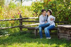 Lovely couple sitting on bench and flirting Stock Photos