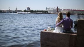 Lovely couple sitting on embankment. At sunny day stock footage