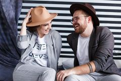Young happy couple sitting on the floor in their flat isolated on striped background in studio stock photography