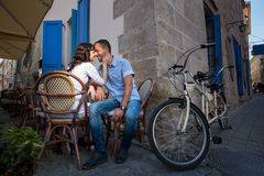 Lovely couple sitting in sidewalk cafe near their tandem bicycle Royalty Free Stock Photo