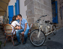 Lovely couple sitting in sidewalk cafe near their tandem bicycle Stock Images
