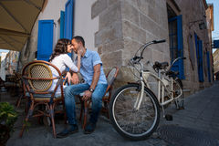 Lovely couple sitting in sidewalk cafe near their tandem bicycle Stock Photo