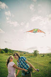 Lovely couple smile at air kite with sky dragon. Lovely couple smile at green meadow with air kite at countryside royalty free stock photo