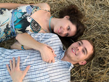 Lovely couple in straw. Lovely young couple lying in straw in filed Stock Photo