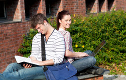 Lovely couple of students sitting back to back. While studying outside their college Royalty Free Stock Images