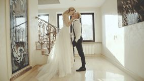 Lovely couple in wedding clothes kisses with smile in luxurious apartment stock video footage