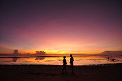 Lovely Couple with Sunrise at Balinese Beach. Stock Photo