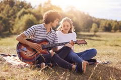 Lovely couple of teenagers spend free time together, have date, enjoys peaceful atmosphere outdoor in meadow. Romantic guy plays g. Uitar and sing songs to his stock image
