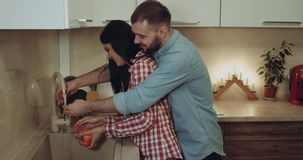 Lovely couple together starts to prepare the dinner together in the kitchen they are playing with each smiling. Red epic stock video footage