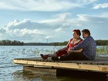Lovely couple together, summer evening. Lovely couple sits on the boat dock, warm summer evening light Royalty Free Stock Photography