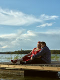 Lovely couple together, summer evening. Lovely couple sits on the boat dock, warm summer evening light Royalty Free Stock Photo