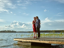 Lovely couple together, summer evening. Lovely couple standing on the boat dock, warm summer evening light Royalty Free Stock Images