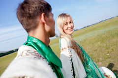 Lovely couple in traditional attire walking outdoors at sunny summer day, stage costume. Stock Photo