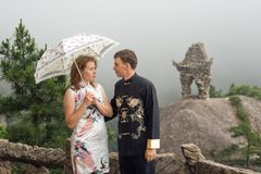 Lovely couple with umbrella at cloudy weather on top of the Chinese mountain Royalty Free Stock Photos