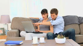 Lovely couple using a laptop stock footage