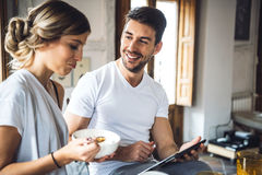 Lovely couple using tablet during breakfast Stock Images