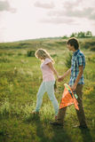 Lovely couple walk at green meadow. Teenage lovely couple walk at green meadow with air kite stock photography