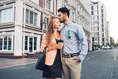 Lovely couple walking around British quarter. Dark-haired man in blue shirt kissing in head blonde girl in black dress royalty free stock photos